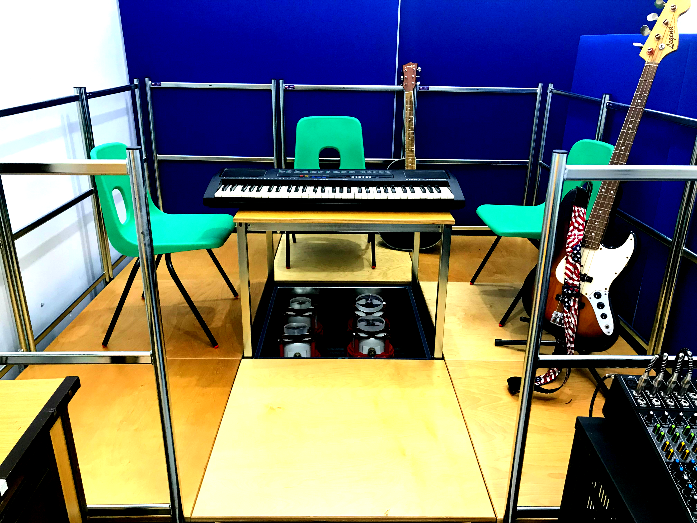 Raised wooden staging area surrounded by a silver coloured balustrade, containing three green chairs, a table with an electronic keyboard  on a central table, a black guitar and a brown and white bass guitar.  Below the central table are four vibrotactile shakers.