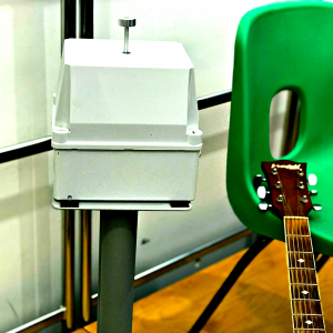 Closeup of a vibrotactile hand shaker next to a green chair. An acoustic guitar neck is resting on the chair