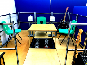 Wide shot of the musical vibrations system. A wooden raised stage, four vibrotactile shakers in a square hole in the middle of the stage, three green plastic chairs, two vibrotactile hand shakers. A black acoustic guitar is also on the stage