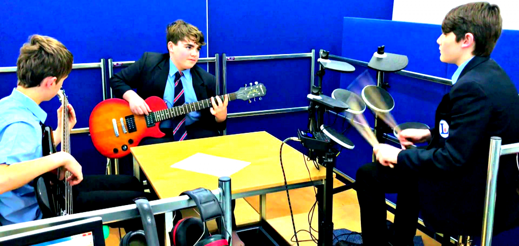 Three teenage boys in blue school uniform. One is playing an electronic drum kit. One is playing an electric guitar. One is playing a bass guitar. The guitarist and drummer are making eye contact. The guitarist and the bassist have their feet upon vibrotactile shakers.