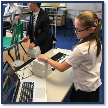 A young girl wearing school uniform in a classroom. She wears a cochlear implant over her left ear. She is using vibrotactile equipment with her left hand and looking at a MacBook screen. Another boy is using vibrotactile equipment with his left hand in the background.